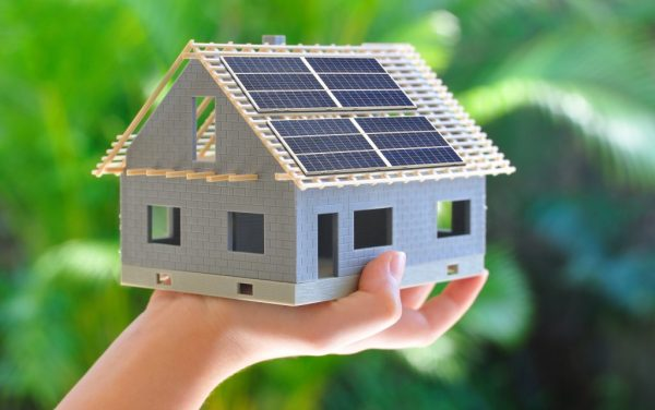 a hand holding a mini solar-powered house