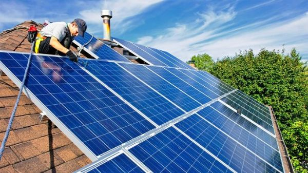 two handymen installing solar panels on a residential roof