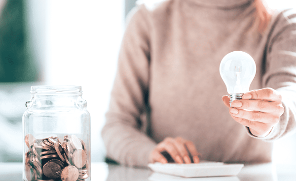 a woman who is enthusiastic about saving electricity is holding a light bulb