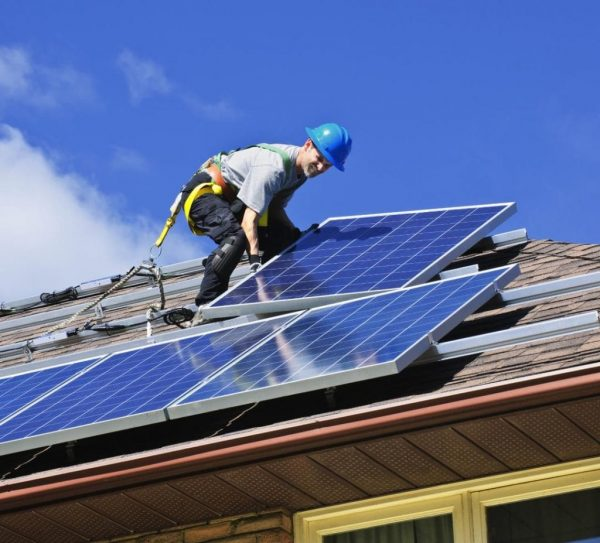 a handyman installing solar panels on a residential roof