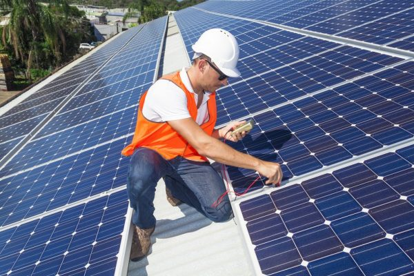 a man doing a maintenance check on solar panels on a roof