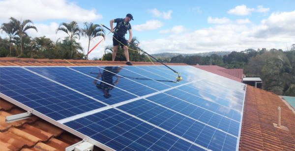 a man cleaning solar panels on the roof