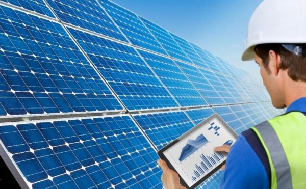 a handyman checking the performance of the solar panels via a tablet