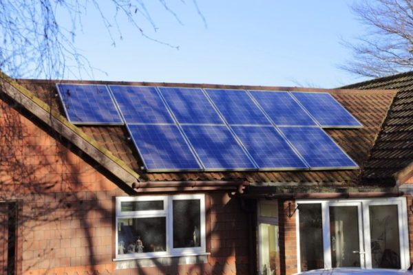 a house with solar panels on its roof under a tree