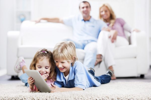 parents sitting on the sofa while their children are lying on the floor and using a digital tablet