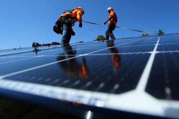 handymen installing solar panels on a roof